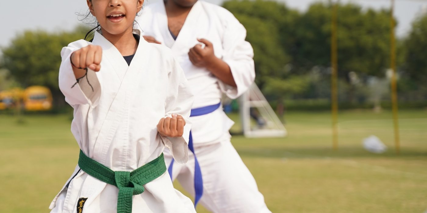 Kids in karate cloths punching to front.